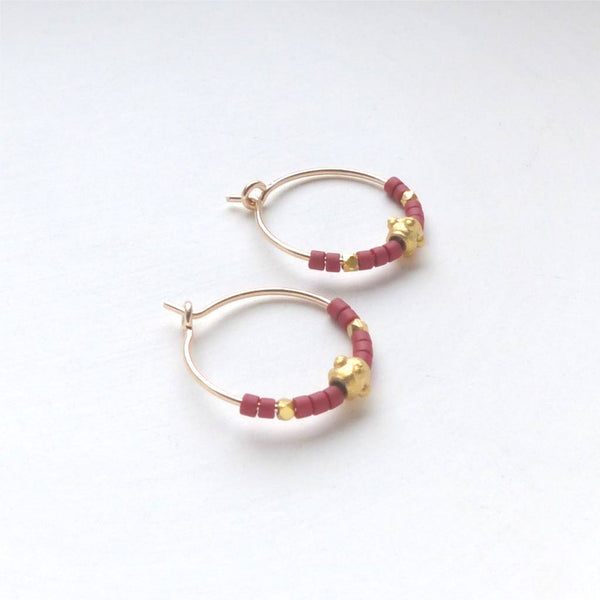 Gold wire hoop earrings with red and gold beads.