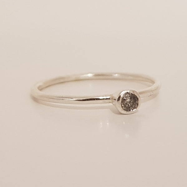 This salt and pepper diamond ring is encased in a silver mount that protrudes from the ring band.