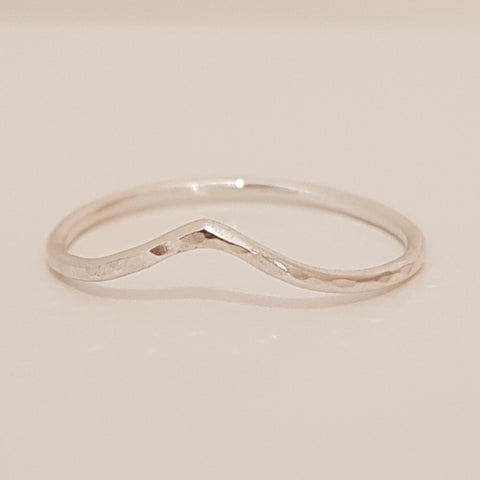 Skinny silver wire hammered ring which has a soft point and textured surface.