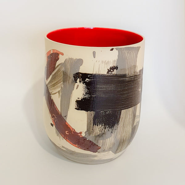 This contemporary vase has a white outer background with a black, grey and burnt orange naive pattern and the inside of the vase is bright red