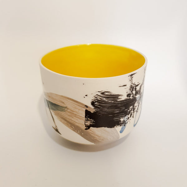 This porcelain contemporary tea bowl has a white outer background with a black naive pattern and a bright yellow inner.