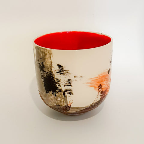 This contemporary tea bowl has a white outer background with a mainly black naive pattern and a bright red inner.