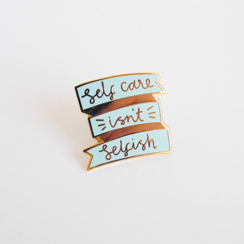 Shing gold and pastel blue pin brooch with the text 'Self Care Isn't Selfish'