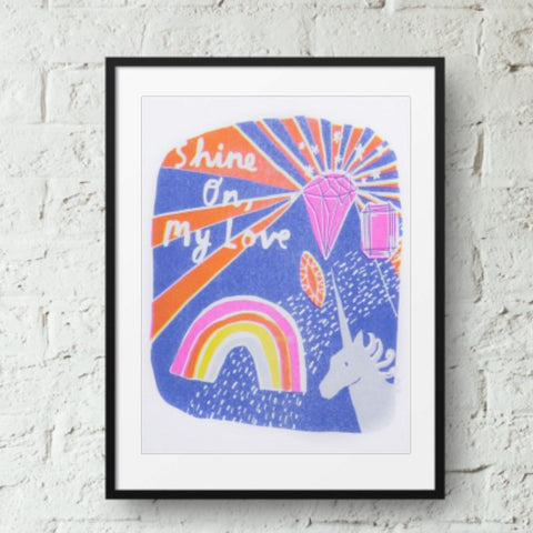 Brightly coloured risograph print featuring a unicorn, gem stones, a rainbow, and the text 'Shine On My Love'