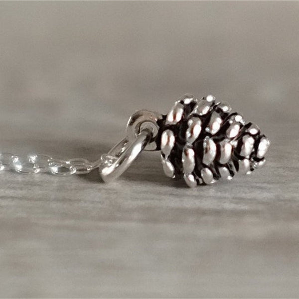 Silver pine cone charm on a silver necklace.