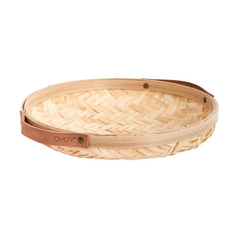 Round woven bamboo bread basket with leather side handles in a natural light wood colour.