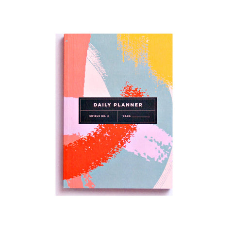 Daily planner book with pink, yellow, blue and coral shapes on cover