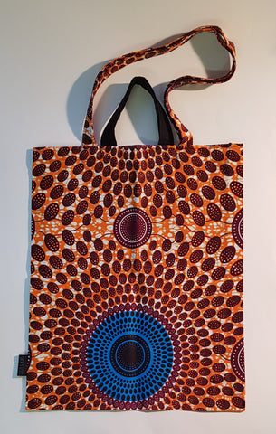 This tote bag has two handles. One is short, the other is long. Vibrant orange. Vibrant blue. Burgundy and white. The pattern is circular.