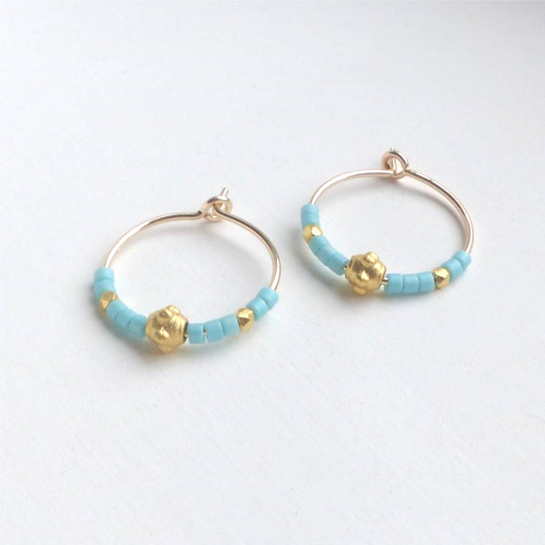 Gold hoop earrings with gold and turquoise beads.
