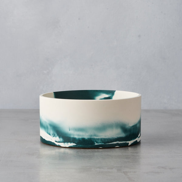 Short sided round dish with a dark green and white coloured  swirled effect