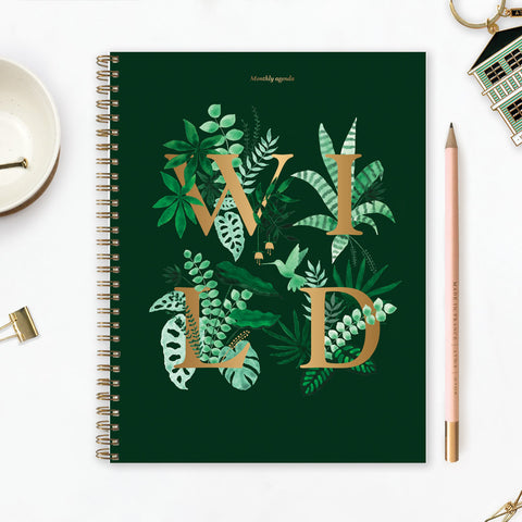 Hard backed 18 month planner with the text WILD printed in gold surrounded by tropical plants and leaves on a dark green background.