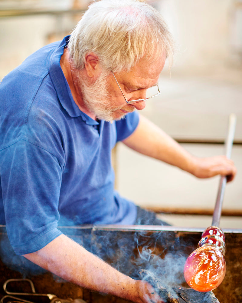 The smoking molten glass base being turned by hand