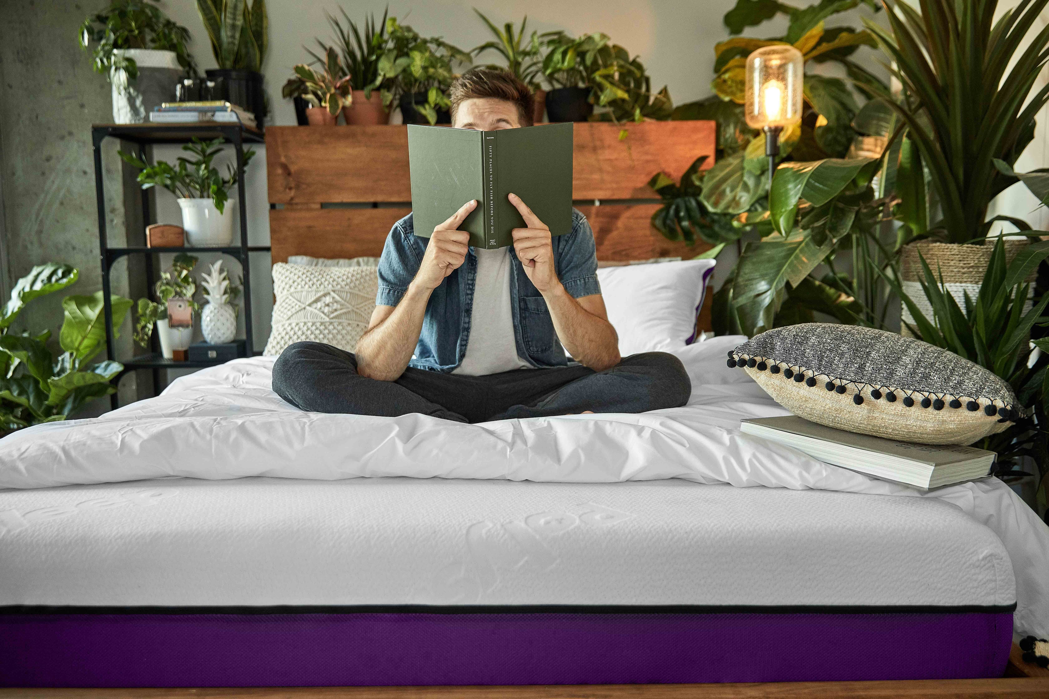 Young man reading a book while sitting on its Polysleep mattress