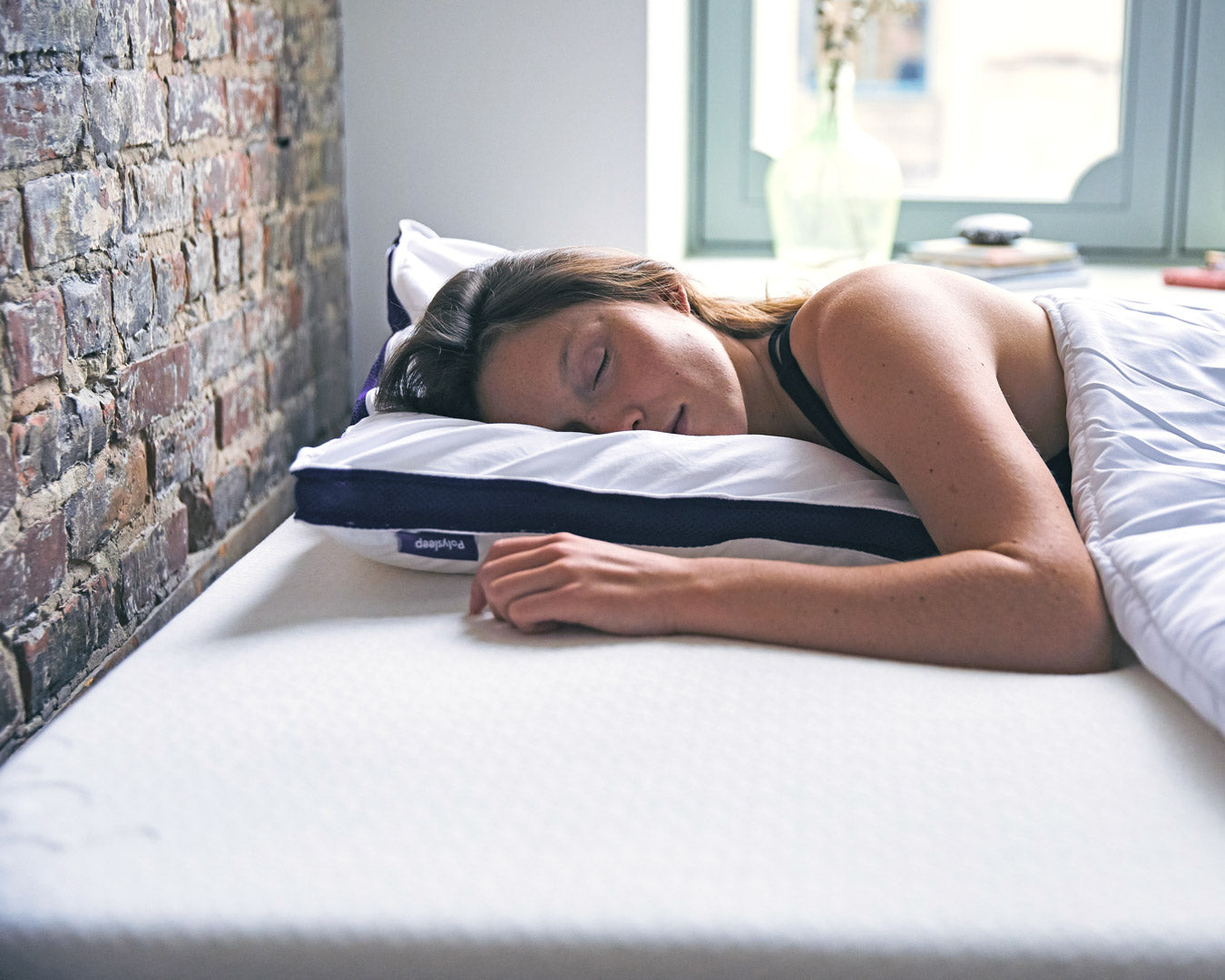 A woman is sleeping on her stomach with a thin Polysleep pillow