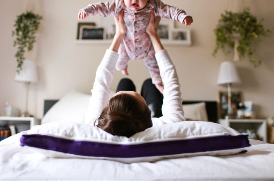 Mom lying on her back on her foam pillow carries her baby in her arms