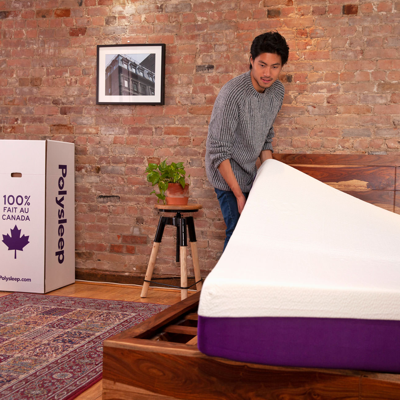 A customer is positioning his new Polysleep mattress on his bed