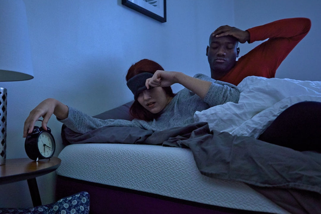 Unrested couple turning their alarm clock off