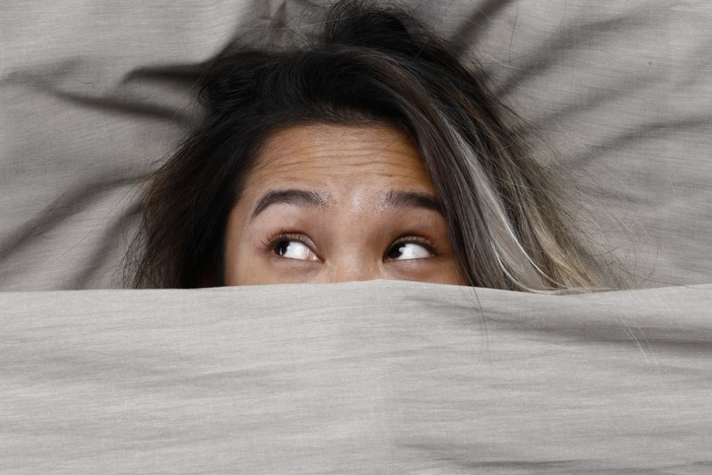 Woman's head sticking out of under a blanket