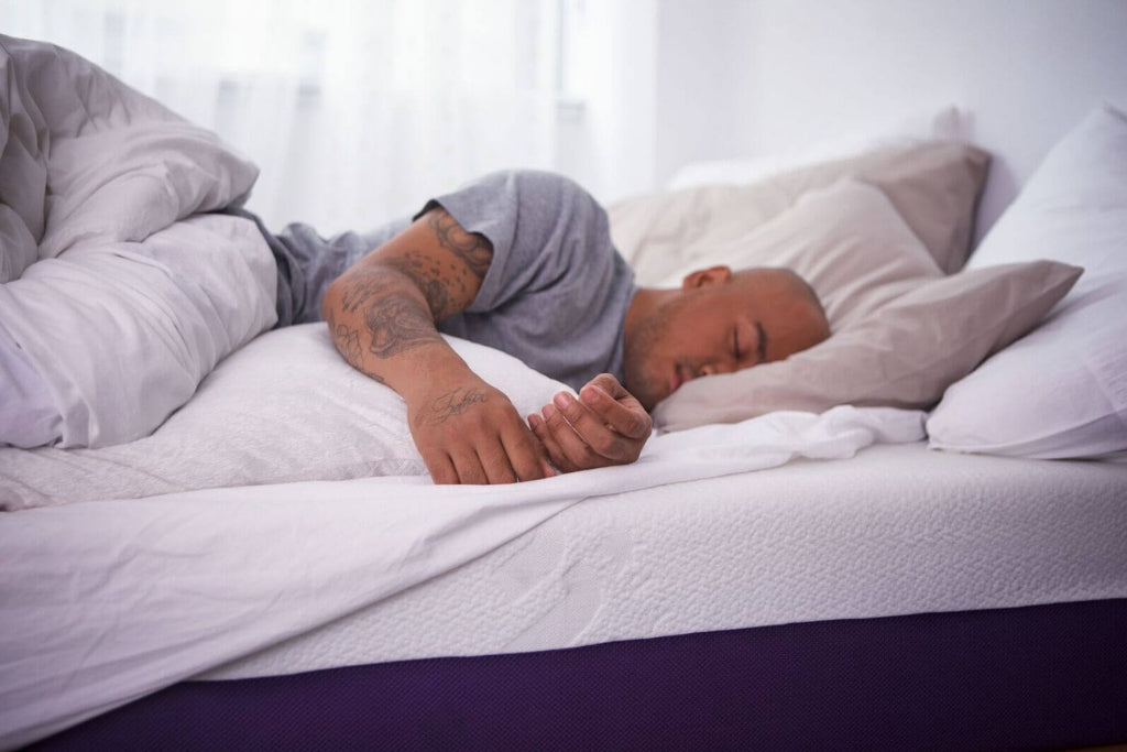 Tatooed man sleeping on a Polysleep mattress