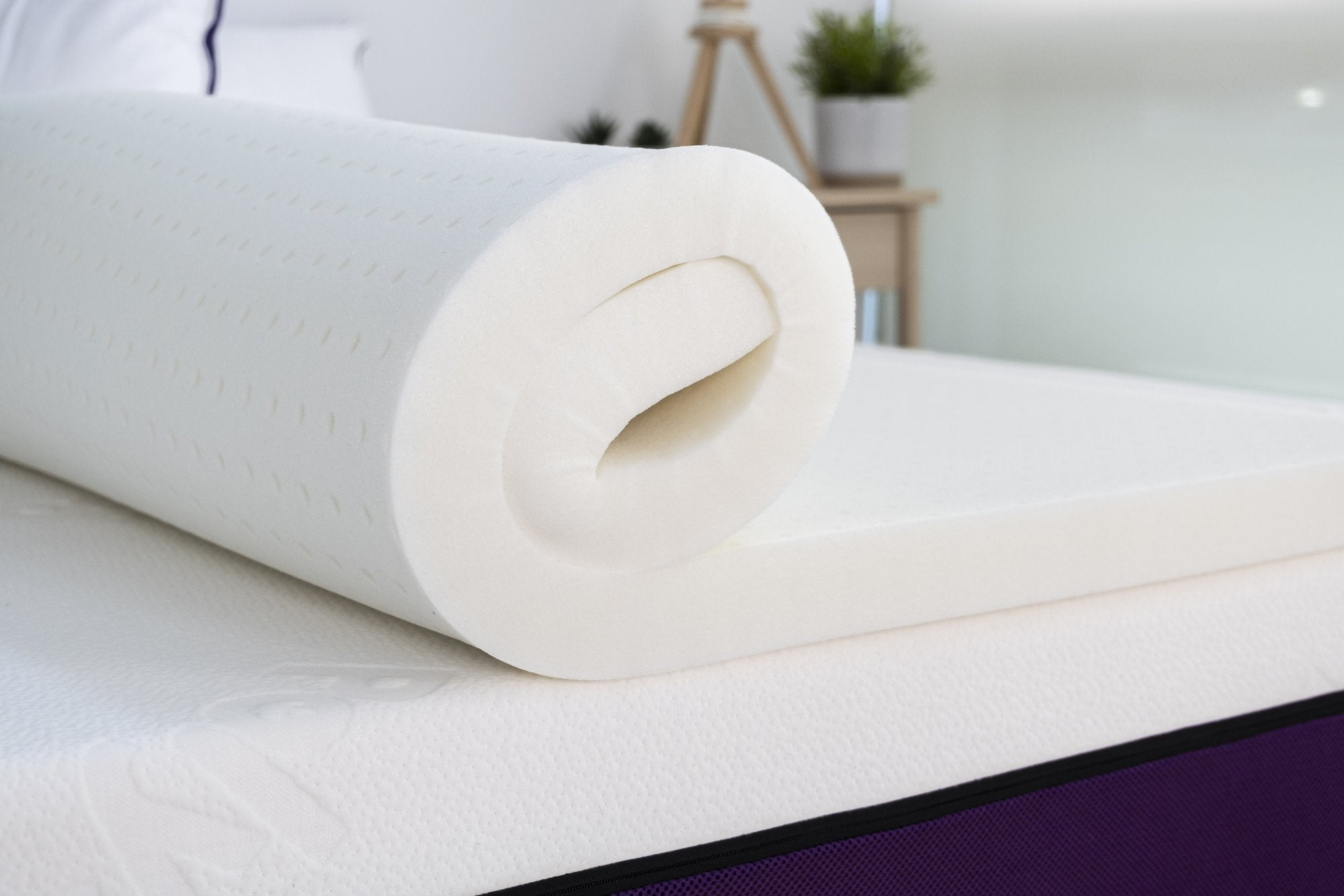 Polysleep antimicrobial mattress topper being rolled out on top of a mattress