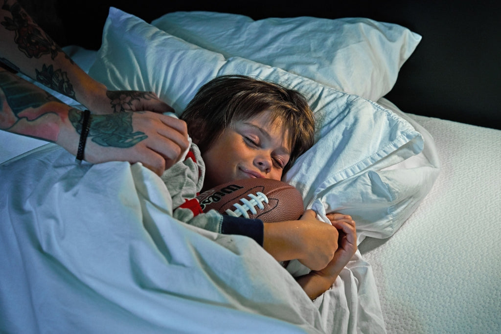 Young boy sleeping with an american football in his hands