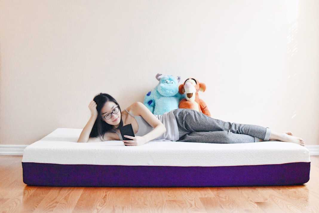 Woman lying on her Polysleep mattress looking at her cellphone