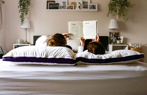 A girl is reading with her mom in bed with the Polysleep Pillows nearby