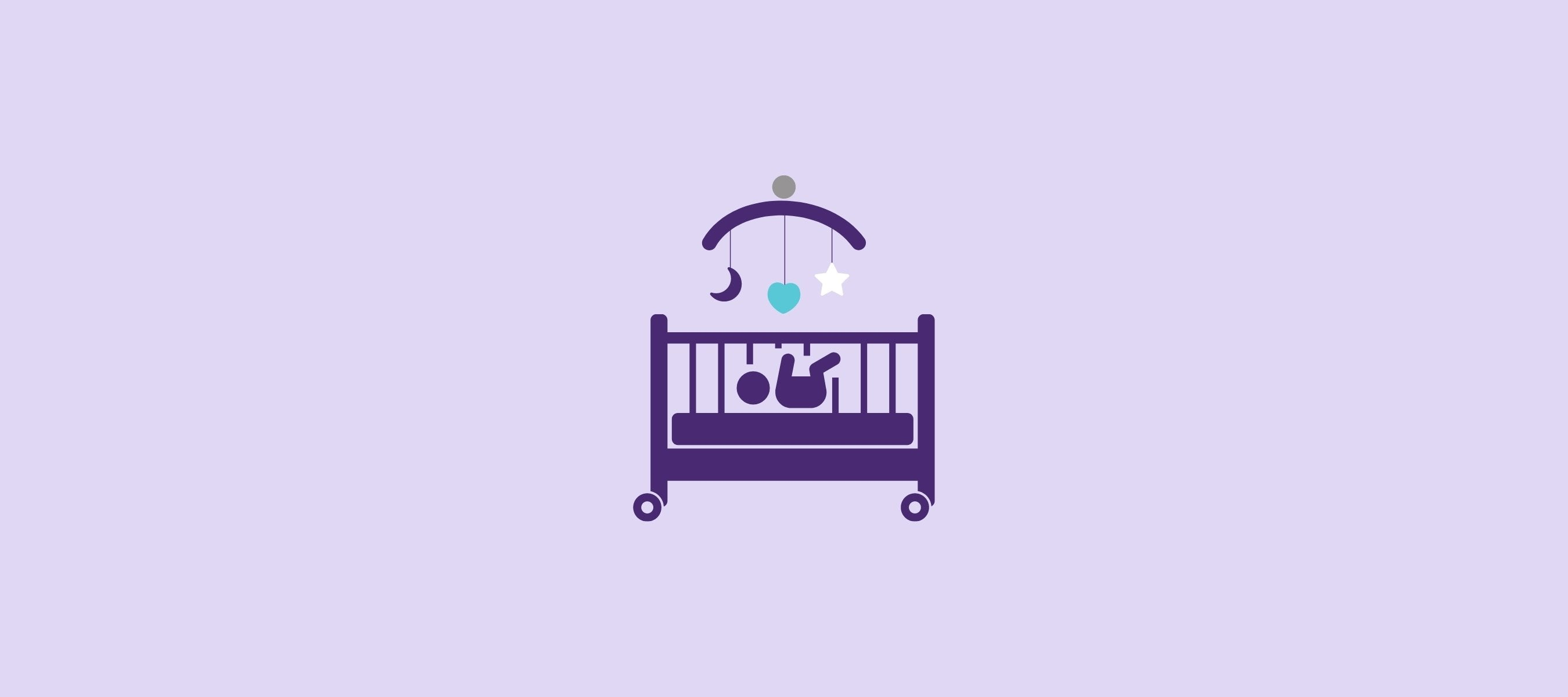 Baby lying in bed with mobile toys hanging above the cradle