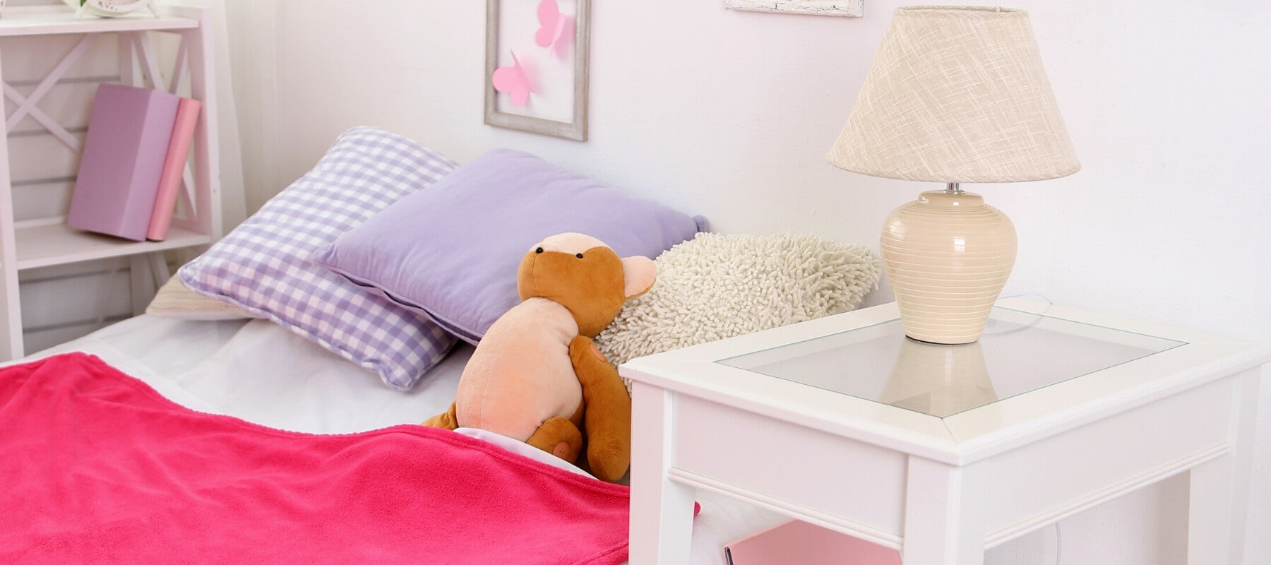 A nightstand next to a child's bed