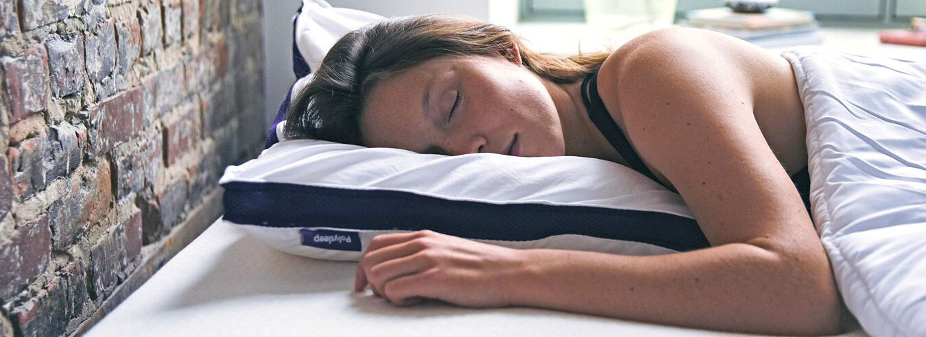 Lady sleeping on a Polysleep mattress with her head resting on a Polysleep pillow.