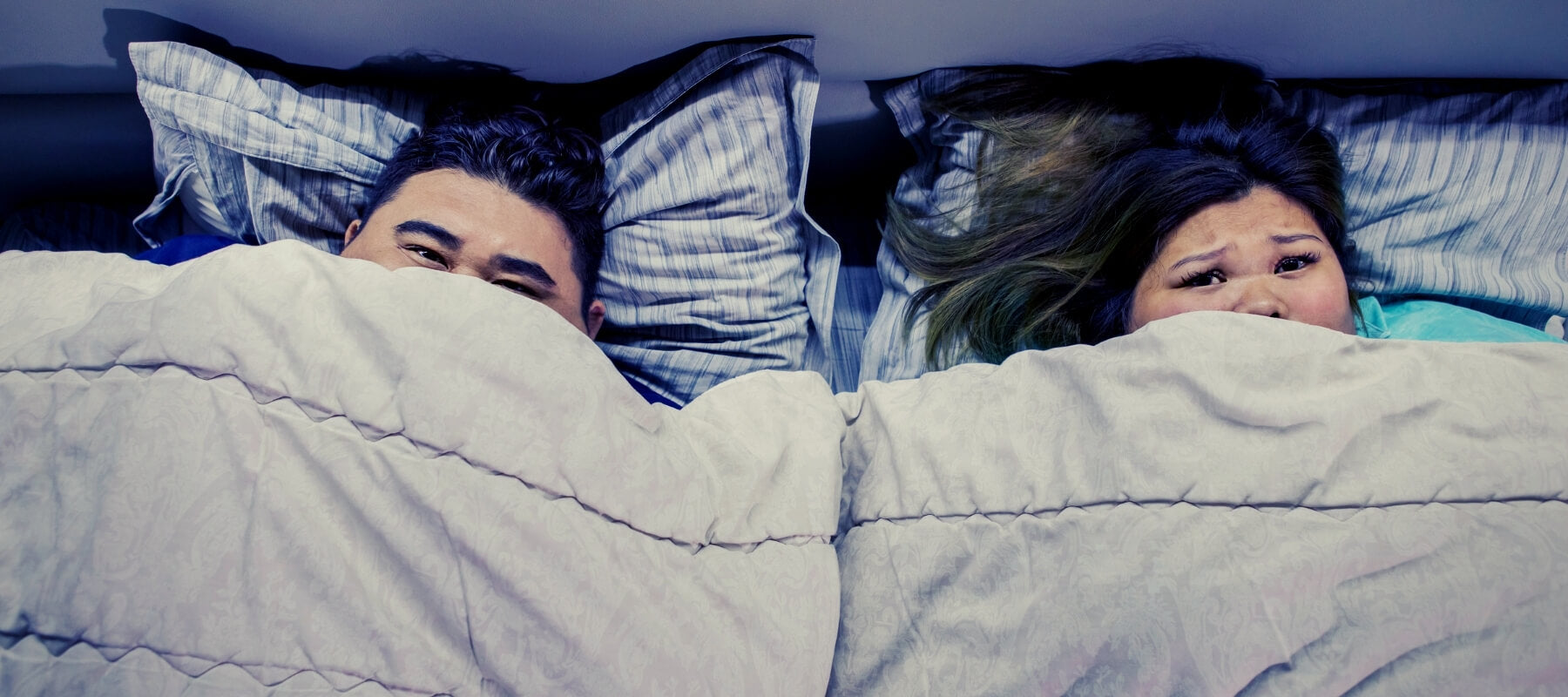 A couple in bed under a heavy sheet also called a weighted blanket