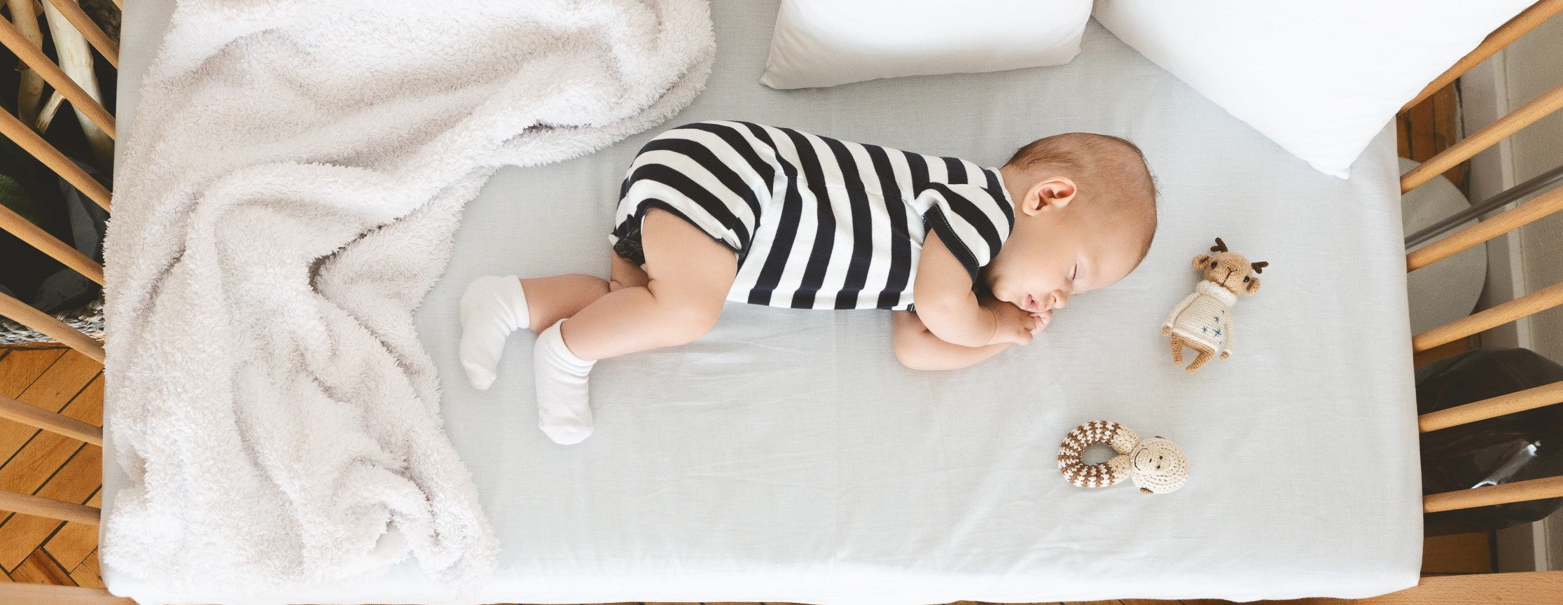 Baby napping on his side in a wooden crib
