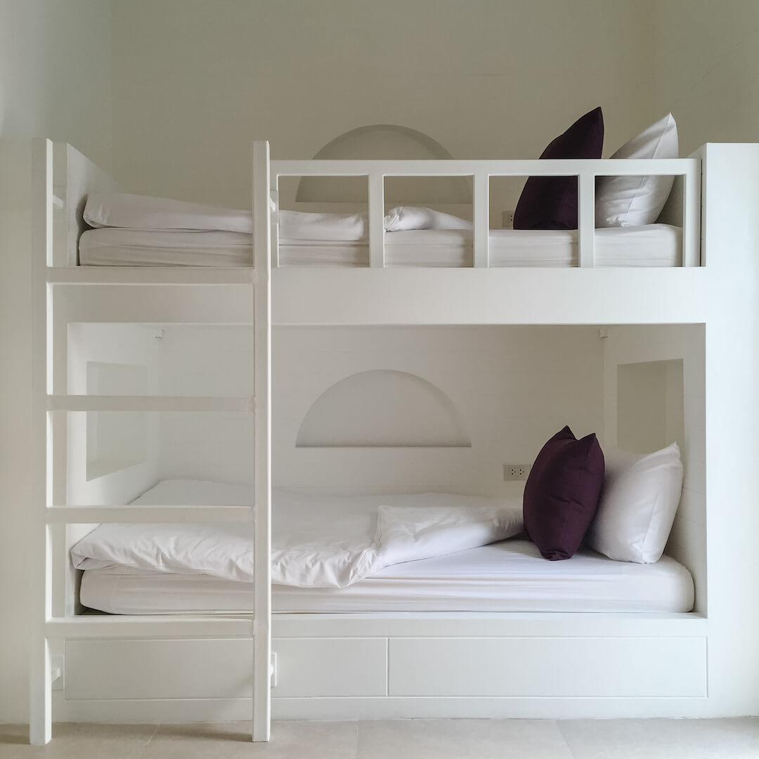 A double-decker white bed including a ladder