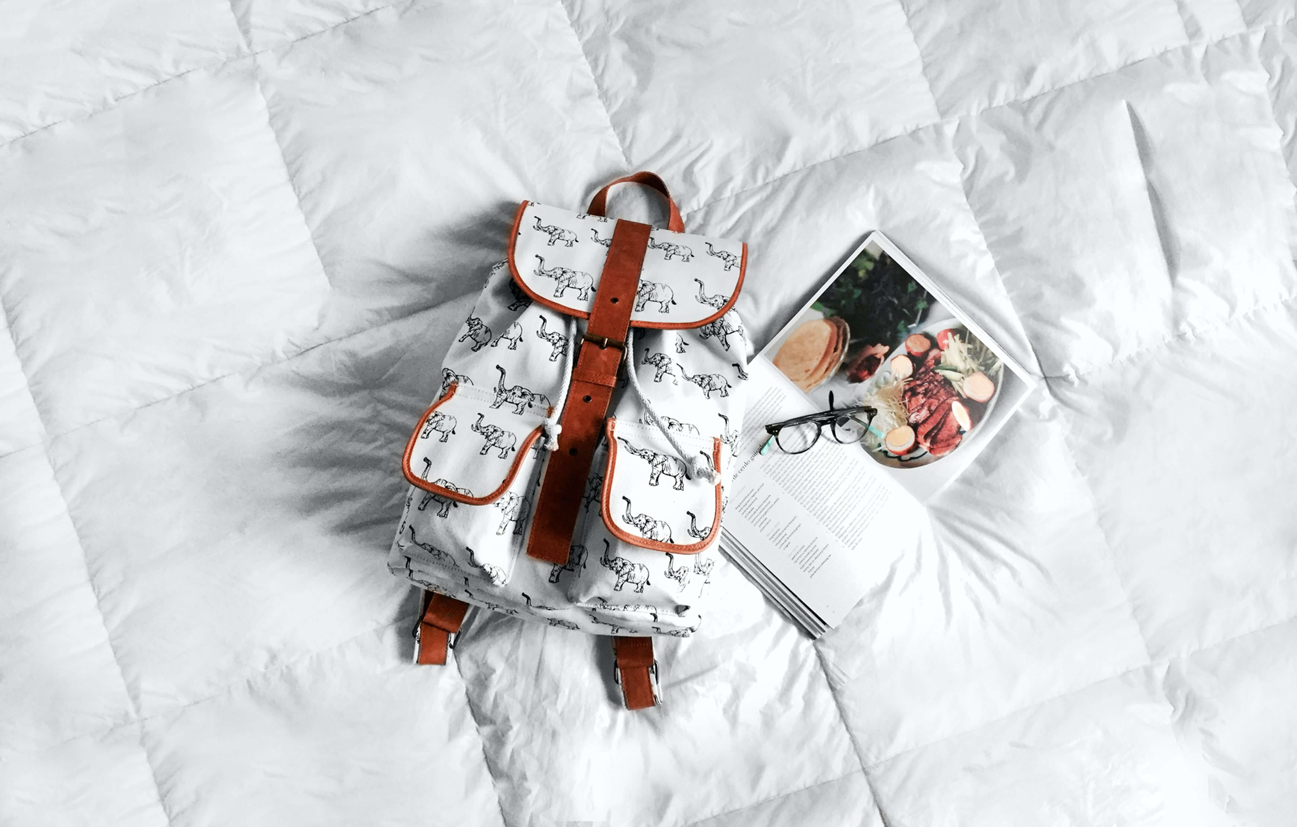 Backpack and school book placed on a duvet bed