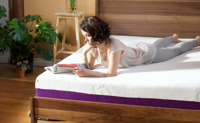 A customer from Halifax is lying on her stomach on the Polysleep foam mattress reading a magazine