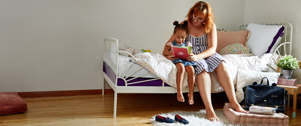 Mother reading a book with her daughter on their Polysleep mattress
