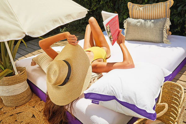A woman tans while reading outside on her Polysleep Mattress