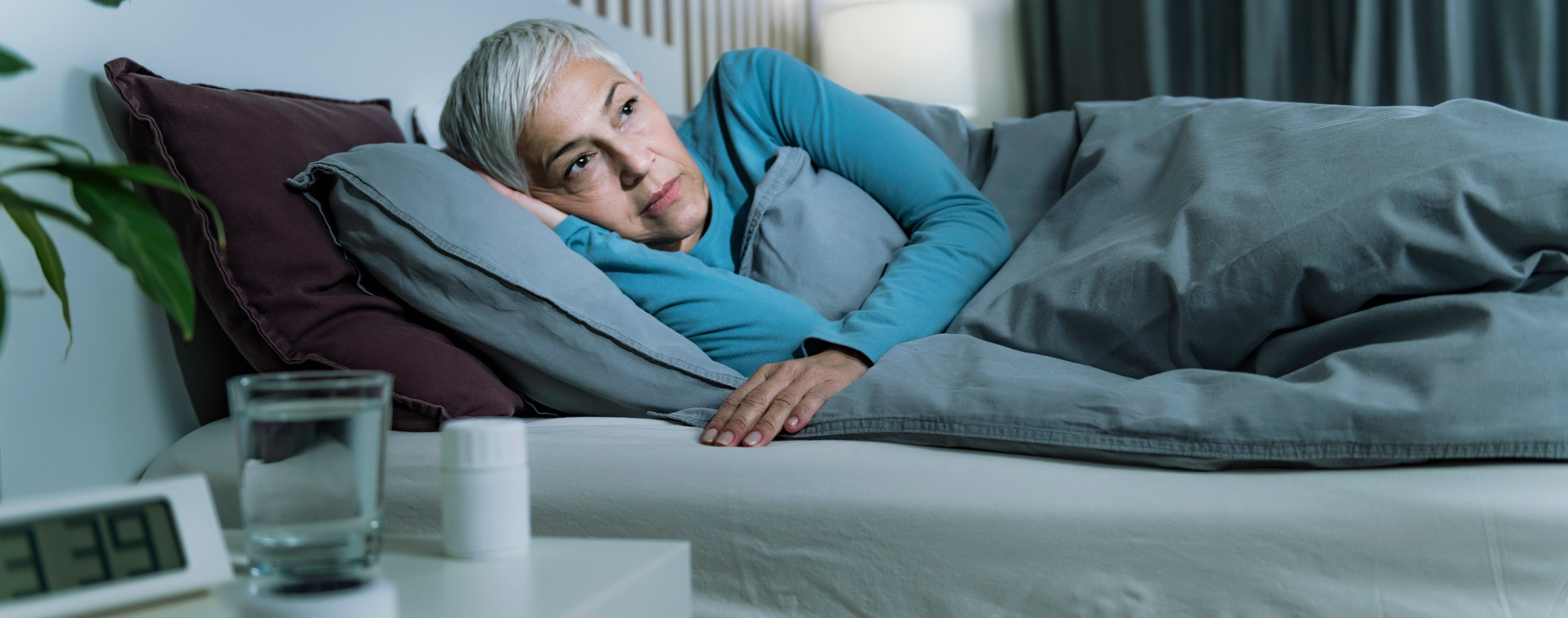 Woman stressed and lying in bed having difficulty falling asleep