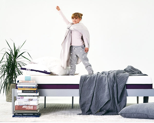 A little girl is playing super hero standing on her Polysleep Mattress