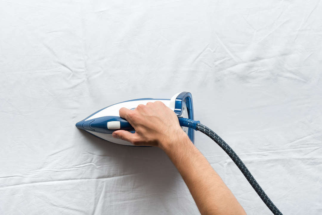 Man smoothing out the flat sheet with the iron