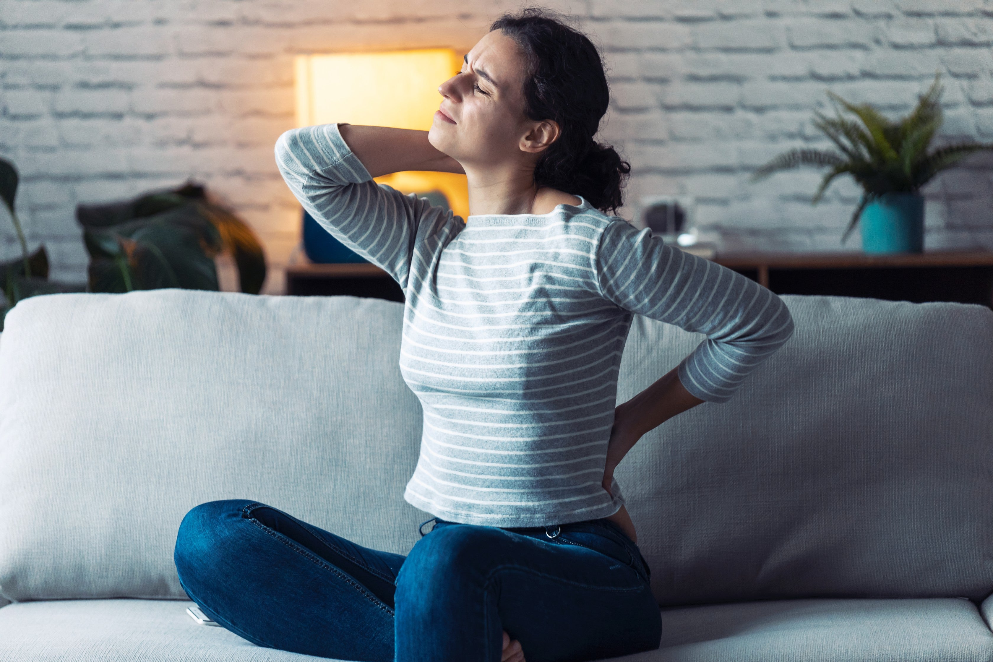 Woman with back and neck pain sitting on the sofa in the living room at home