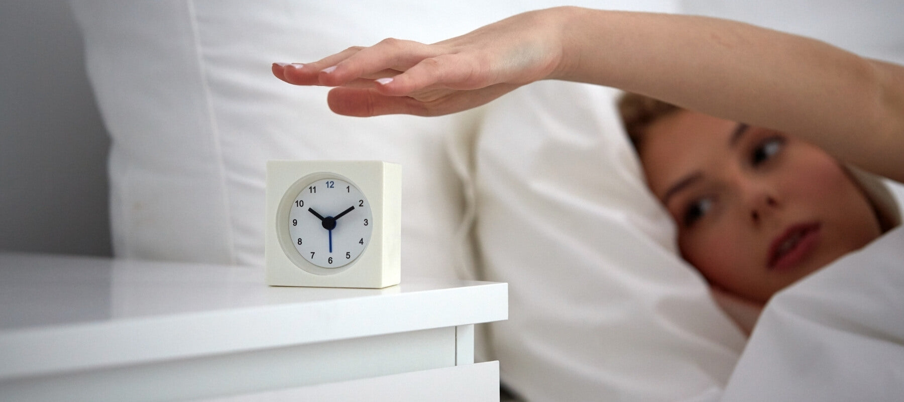 Woman lying in bed, closing her alarm clock on the bedside table