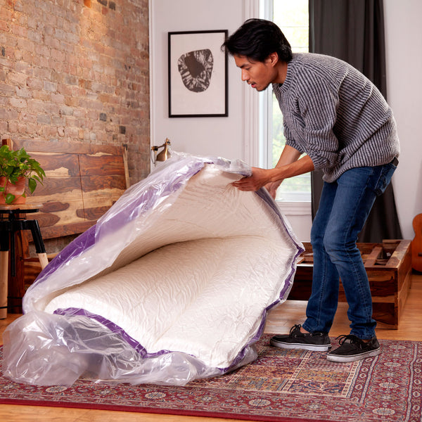 A man is unrolling his Polysleep foam mattress and is preparing to install it in his room in Oshawa