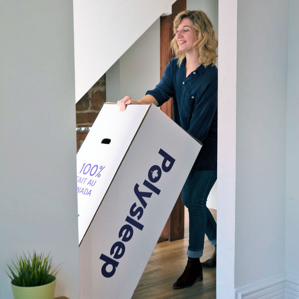 Blond woman receiving her new mattress in a box in Windsor