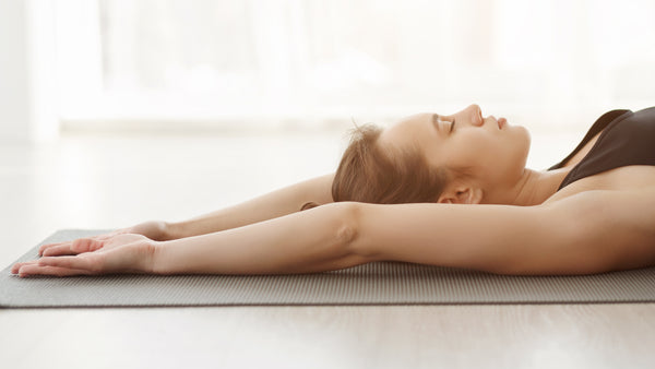 Youg woman doing breathing exercise on a yoga mat.