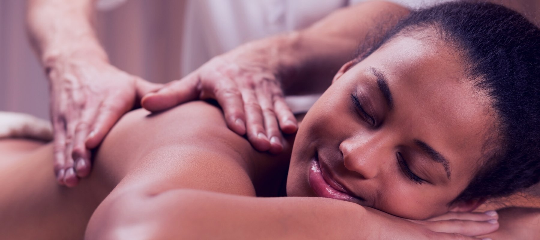 Woman relieving her shoulder pain by massage therapy