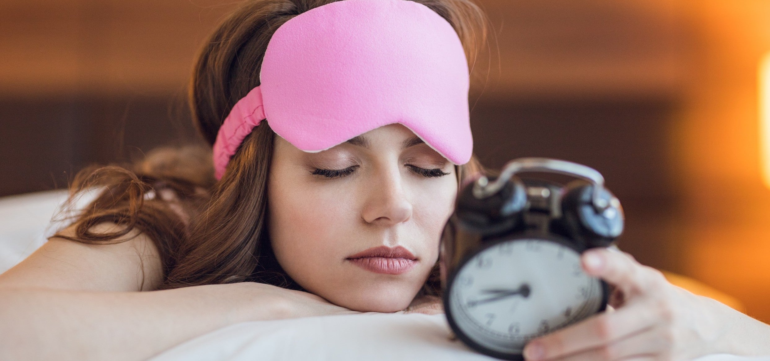 Young lady with a sleep mask on her forehead, dozing off on her bed while holding an alarm clock