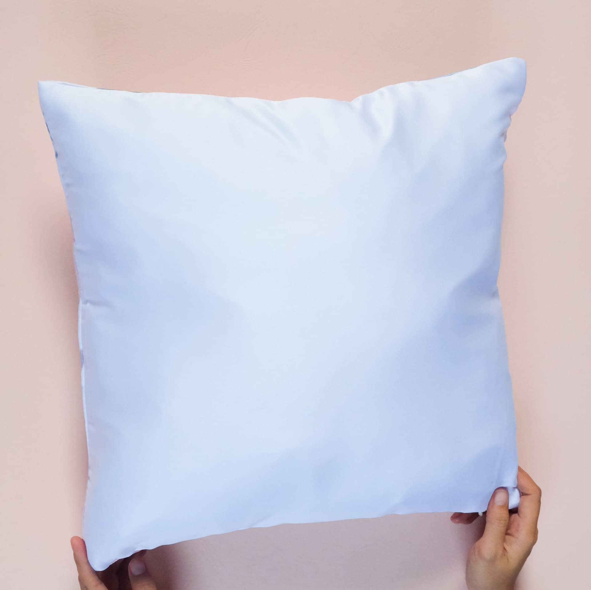 White pillow on pink background