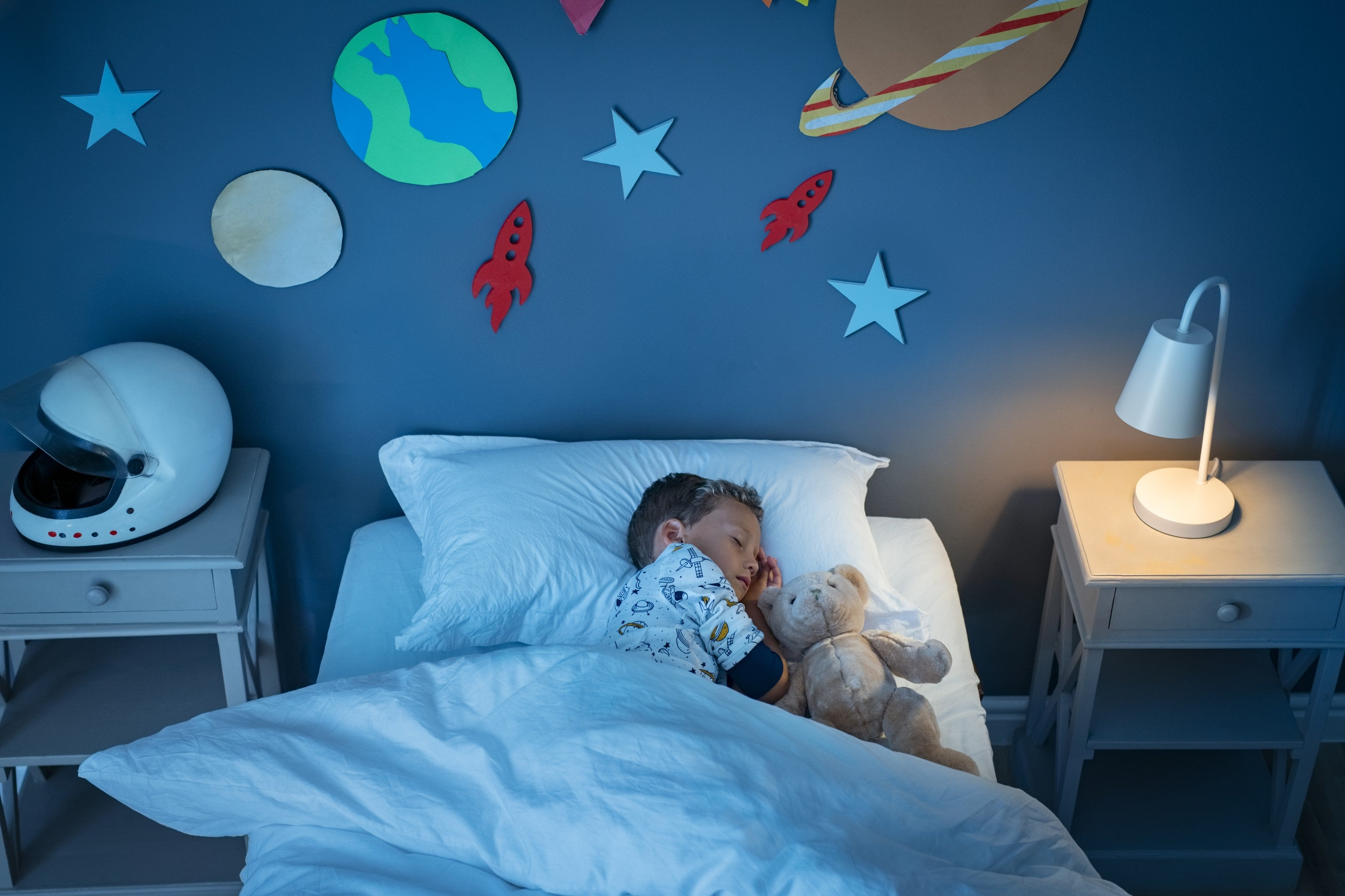 Young boy asleep in his bed with a light on