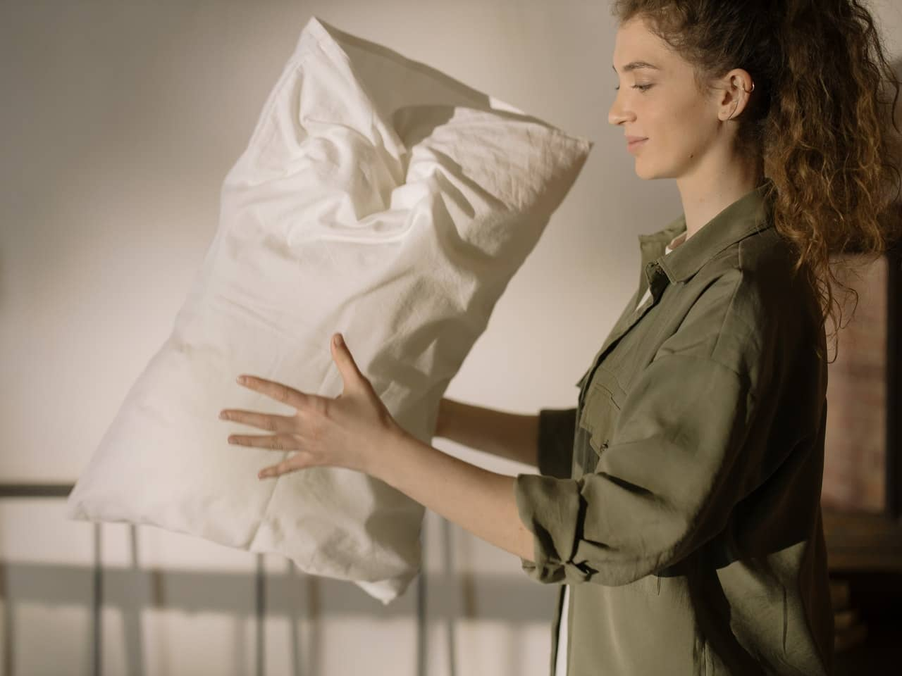 Young woman shaking a pillow